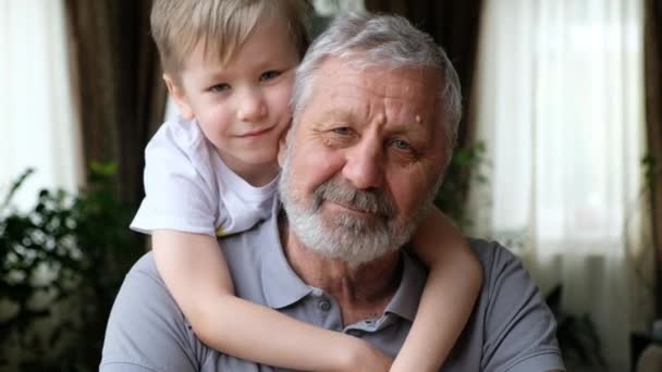 Senoir elderly happy man grandfather with grandson boy looking at camera, smiling and hugging