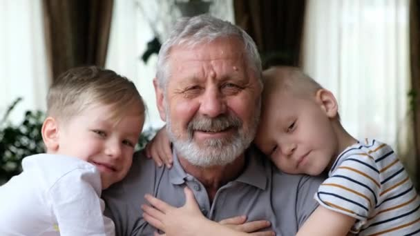 Senoir elderly happy man grandfather with grandsons boys looking at camera, smiling and hugging