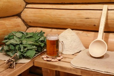 On the bench in the Russian bath  are bath utensils and a mug of light beer.