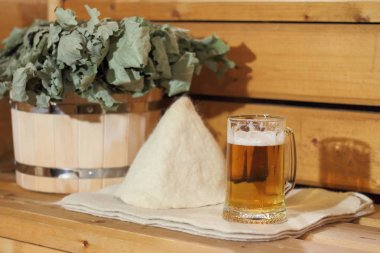 A mug of light beer and bath accessories are in the interior of the Russian bath.