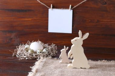 Easter composition with quail eggs and wooden figures of hares on a dark wooden background.