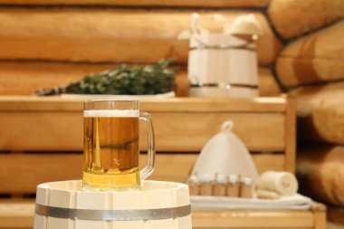 A mug of  light beer on a barrel in the sauna on the background of bath accessories.