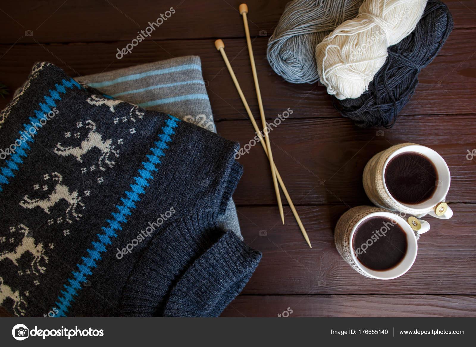 134855299bb Χειμερινά Αξεσουάρ: πλεκτά ενδύματα, δύο φλιτζάνια καφέ, μπάλες από νήματα  και βελόνες για