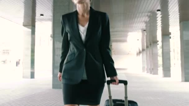 Close-up of a confident blond businesswoman walking with trolley in the urban environment