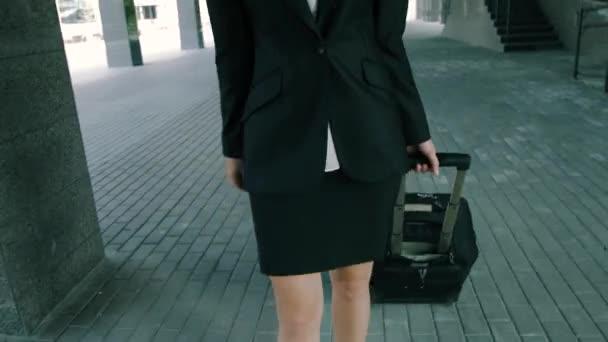Detail o atraktivní blonďatá moderátorka chůzi s cestovních zavazadel do úřední budovy