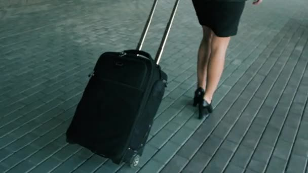 Štíhlá žena nohy v černé vysoké podpatky obuvi chodit s cestovních zavazadel