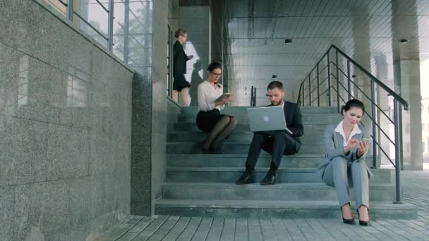 Business people working on staircases by office building using different gadgets