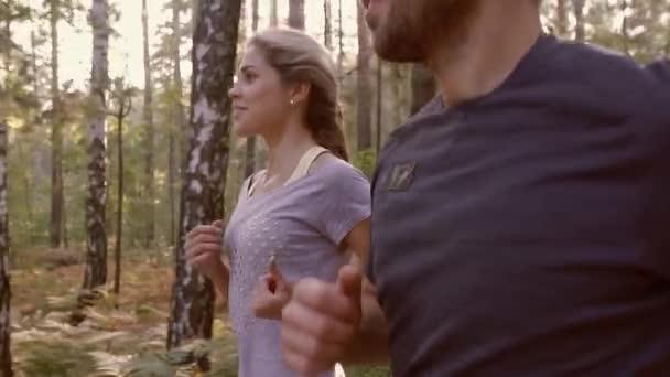 Közeli kép a kocogás együtt, az erdő, a fiatal pár