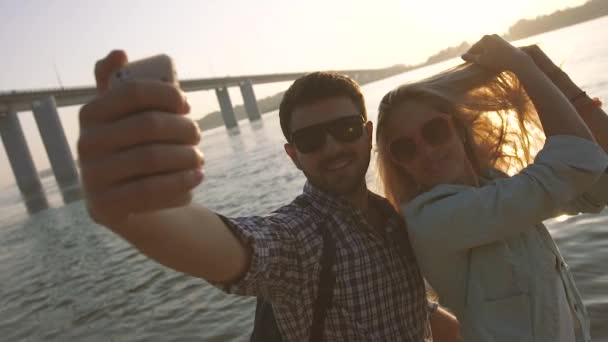 Happy couple in love taking selfie photo near the river on a wonderful evening