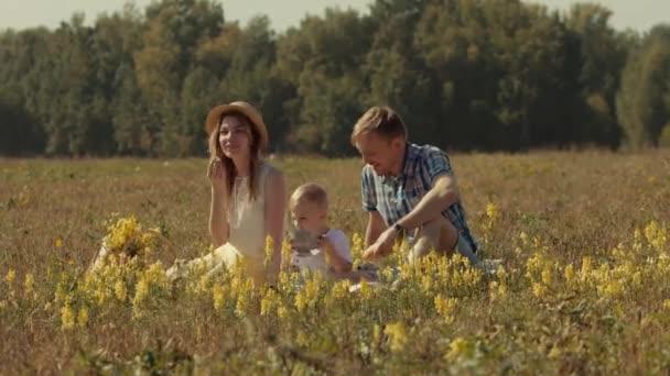 Mladí rodiče mají rodinný piknik s jejich malého syna