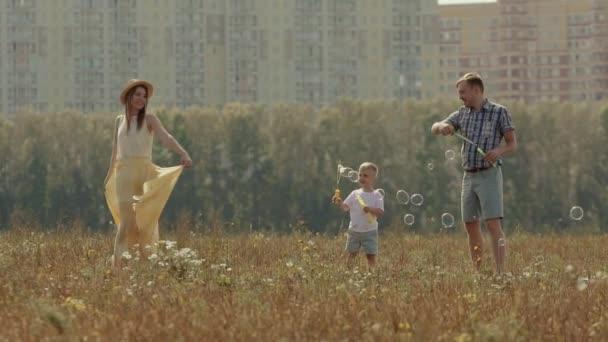 Mladou rodinu tří lidí se těší slunečný den. Otec a jeho šťastná