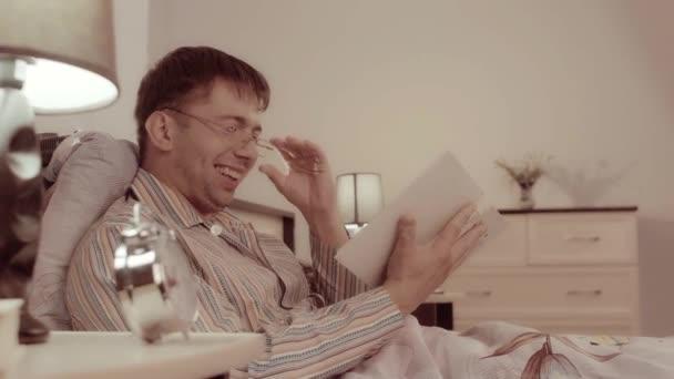 Muž v brýlích sedí v posteli s knihou a směje se jeho potěšení