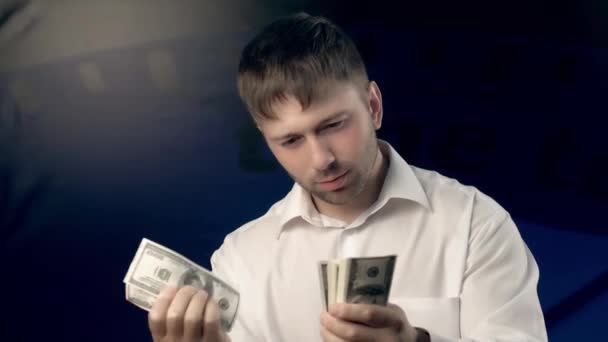 Concentrated young man counts a certain amount of money for someone and reaches out a hand with money