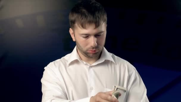 Portrait of serious young man getting some dollars out of his pocket, counting certain amount of money and giving it to someone