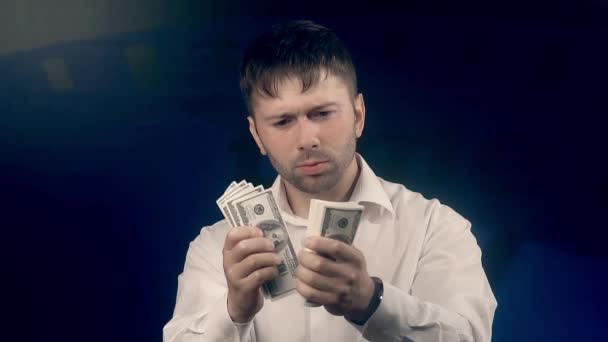 Portrait of young handsome man counting money for someone and giving them to the camera