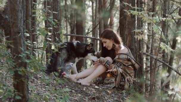 Beautiful young woman in ethnic clothes feeding her wild dog