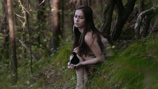 Furcsa és koncentrált fiatal nő visel szőr tetején az erdő a dombon ülő és a gondolkodás