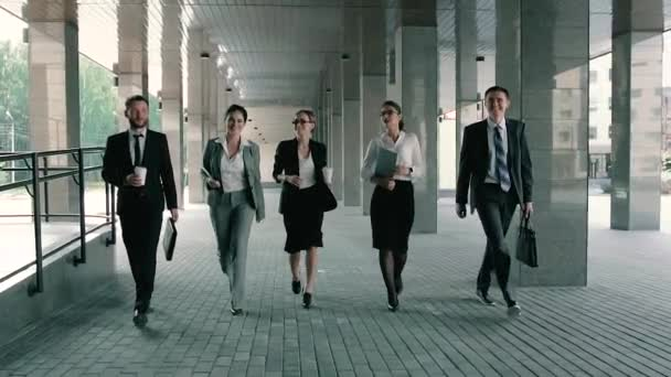 Group of five business people pleased and confident walking in business centre arcade