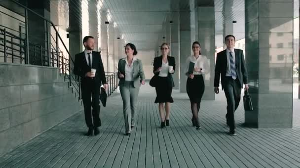 Five business coworkers walking towards the business center friendly talking to each other