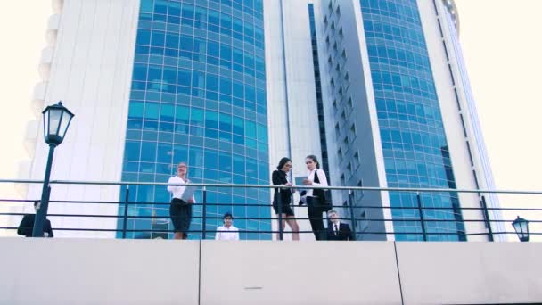 Business women and business men talking on terrace. From below shot