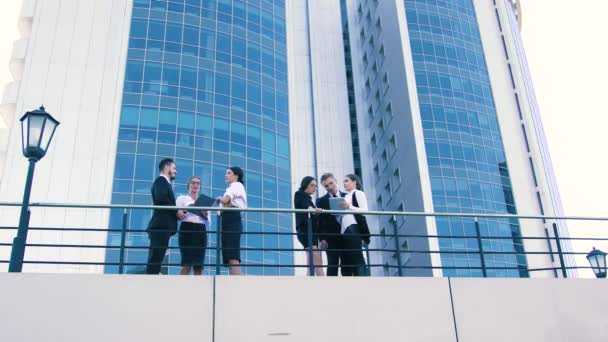 Two companies of coworkers standing on terrace and discussing the results of their researches