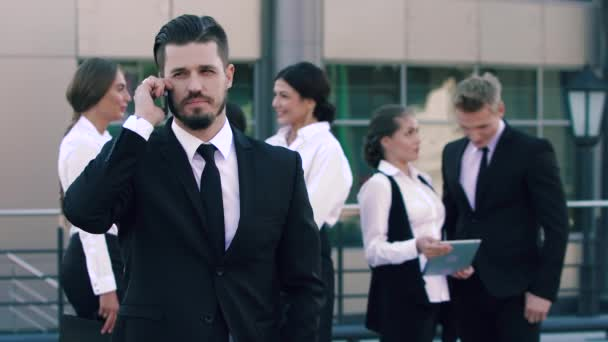 Portrait of serious but pleased business man making a phone call and four business coworkers standing in the background