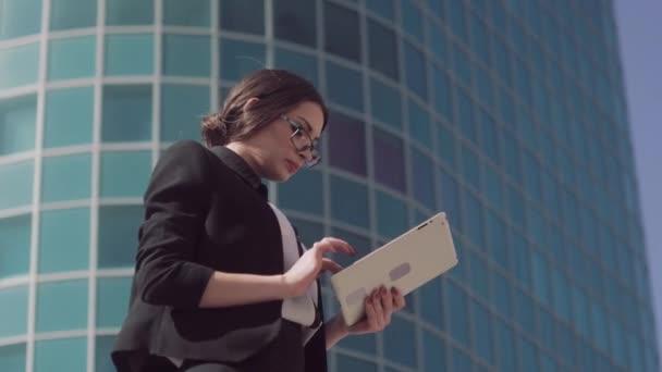 Mladá koncentrované obchodních žena pracující na tabletu při čekání na klienty na místě srazu