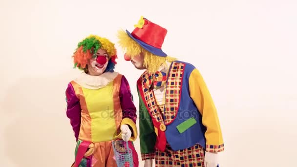 lustige Clownin neckt den männlichen Zirkusclown, indem sie ihm nicht das Spielzeug-Zuckerbrot gibt