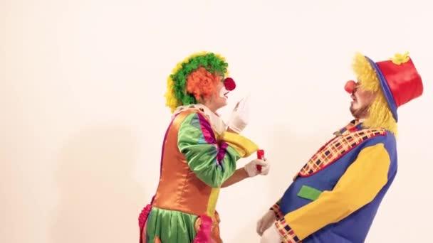 fröhlicher junger Clown überschüttet einen anderen Zirkusclown mit Seifenblasen
