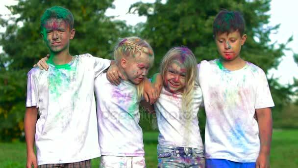 Ritratto di quattro bambini: due ragazzi e due ragazze bionde in piedi davanti alla telecamera che abbracciano e che ridono