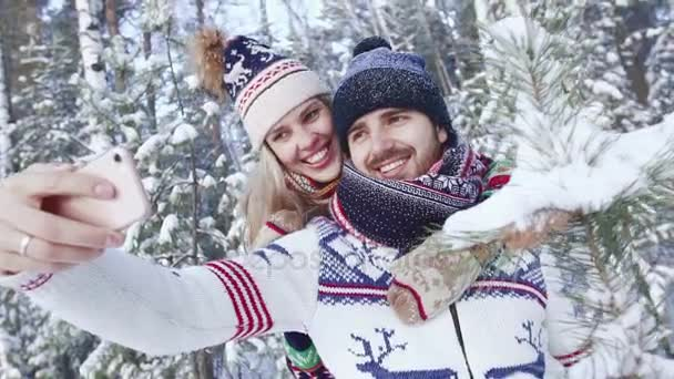 Loving couple in the snowbound forest taking photos together