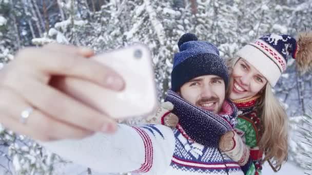 Mosolygó szép pár vesz selfie Hófúvásából fa