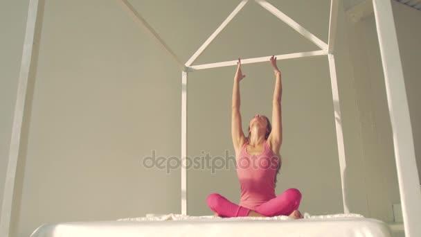 Hezká mladá žena sedí v lotosové pozici