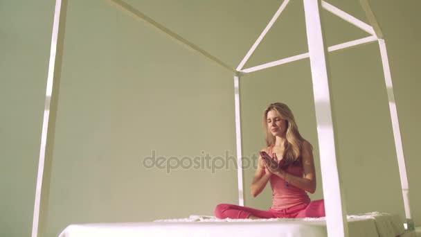 Jóga žena v posteli v lotosu představují meditaci