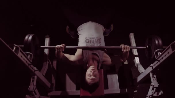 Athletic young fitness man practicing bench pressing with heavy barbell