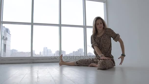 Porträt einer Frau, die Yoga allein im Studio vor Fensterhintergrund praktiziert