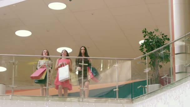Three attractive women meeting in shopping mall and showing their purchases