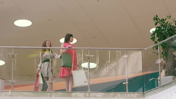 Three beautiful women meeting in shopping center and starting to discuss their purchases