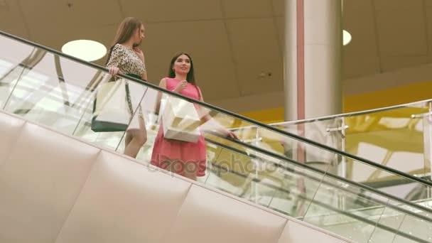 Dvě krásné ženy stojící na po eskalátoru nákupní centrum
