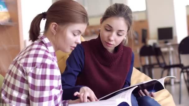 Dvě dívky studují vědeckých knih v knihovně