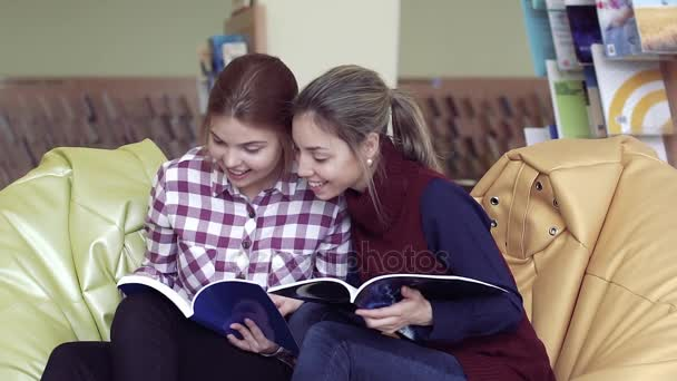 Two pretty university girls sitting in library and looking into books