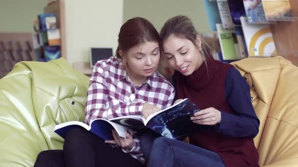 Two smiling female students thumbing through funny magazines