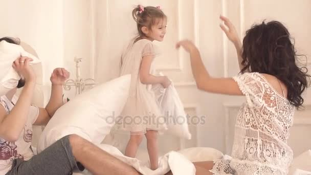 Happy funny family having a pillow fight in bed
