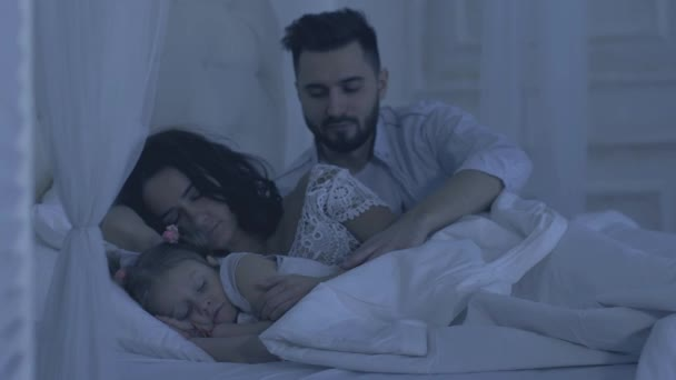 Tender caring father hugging and kissing his family before falling asleep at night