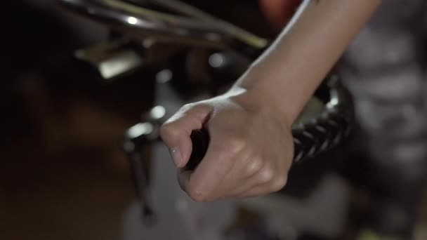 Close-up of hands of a woman holding the handles of stationary bike