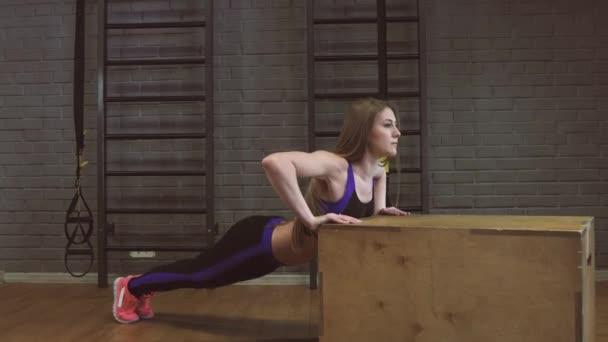Tělocvičně žena push-up síla kliky v fitness cvičení