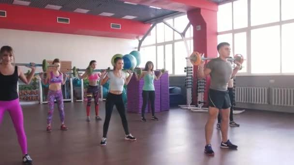 Fitness, sport, výcvik - skupina ženy a muže s činky v posilovně