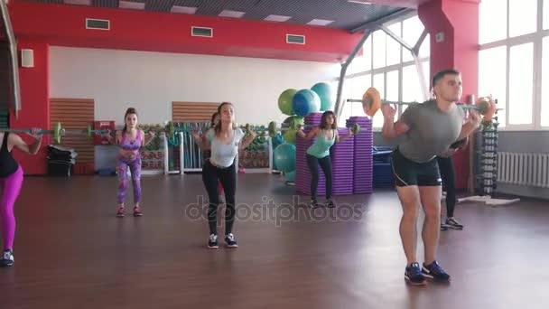 Kas závažím na tréninku. Skupina mladých žen a muž v provedení cvičení aerobiku. Dívky s činky. Zdravý životní styl ve fitness centru