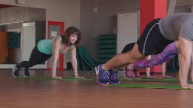 Group of people training in a gym - Personal trainer and sportive persons in a fitness class