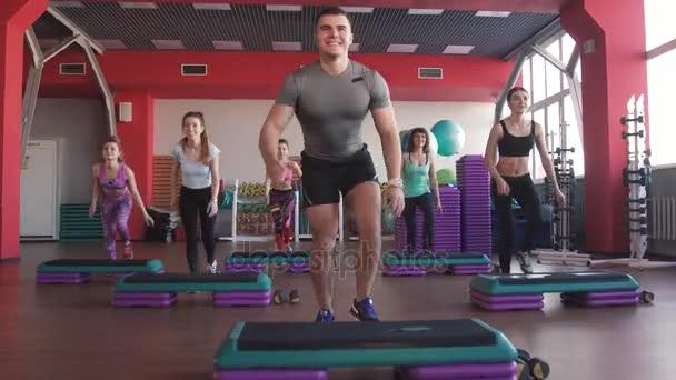 Step aerobik gyakorlása osztály - embercsoport gyakorlása a Lépcsőzők a tréner